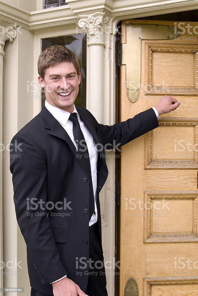 Confident Man Arriving: Smiling Salesman Knocking on Front Home Door stock photo