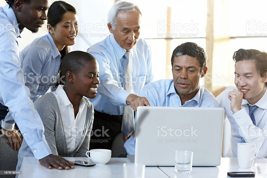 Confident man discussing with colleague a project pointing at laptop royalty-free stock photo