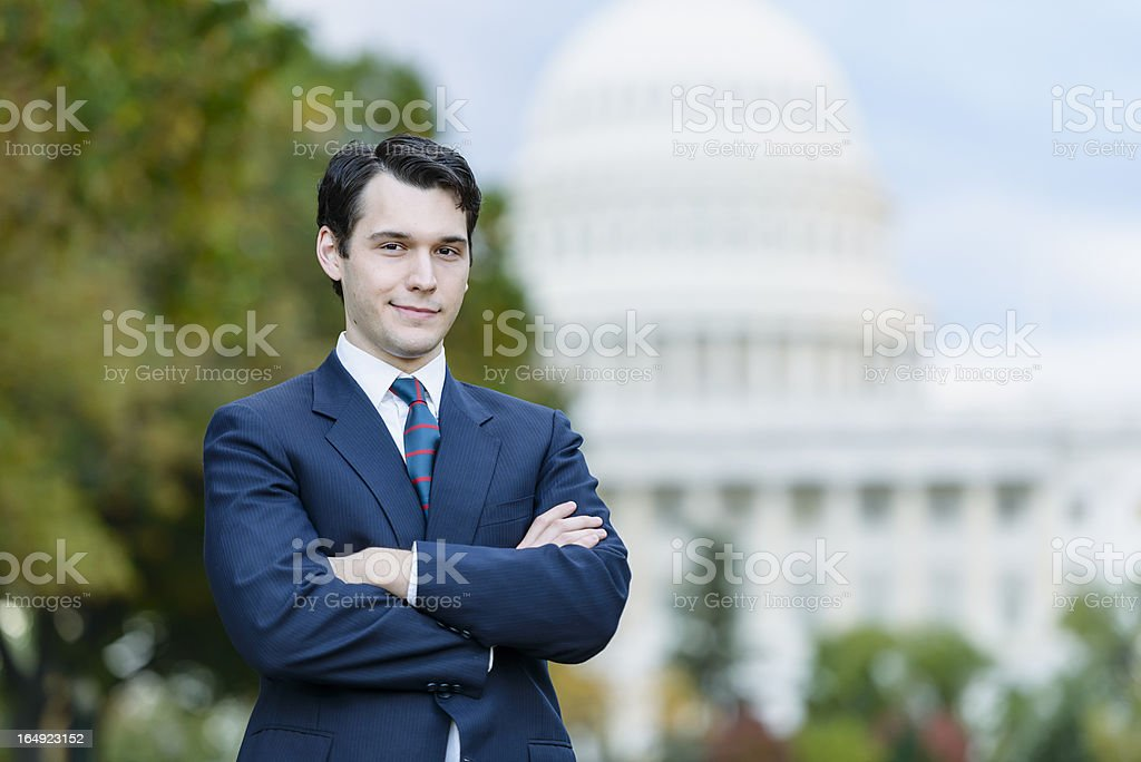 Confident man in suit standing in front of US Capitol stock photo