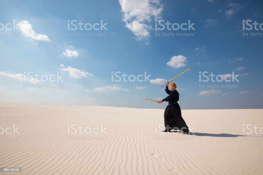 Confident man practicing with a training sword in desert stock photo