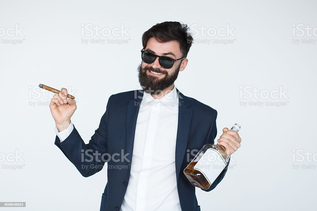 confident man smoking a cigar and drinking whiskey stock photo