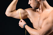 Confident man taking measurements of muscles