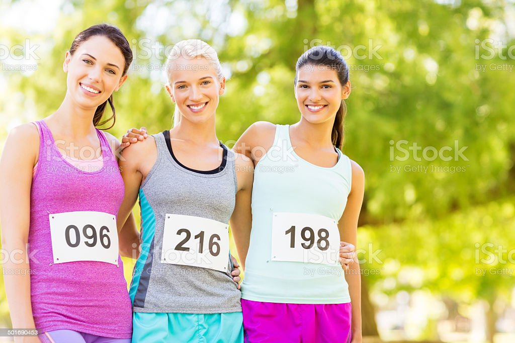 Confident Marathon Runners Standing Arms Around In Park royalty-free stock photo