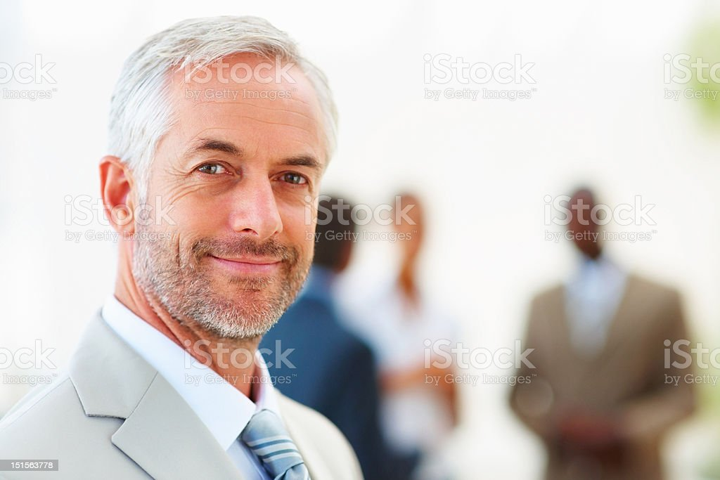 Confident mature businessman with colleagues standing in background royalty-free stock photo