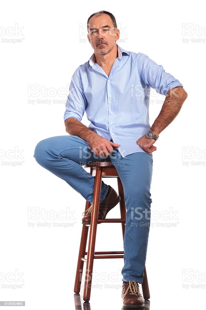 confident mature casual man posing seated on chair stock photo