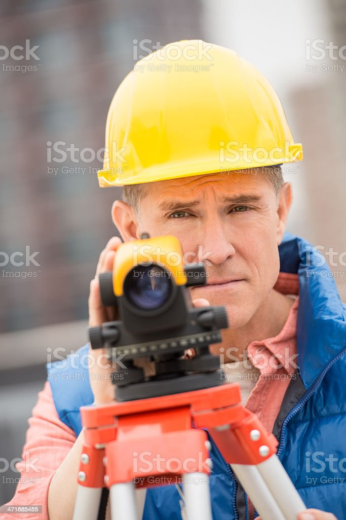 Confident Mature Construction Worker With Theodolite royalty-free stock photo