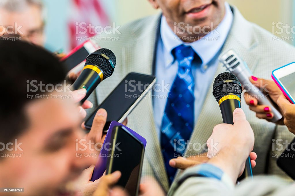 Confident mature political candidate answers reporters' questions stock photo