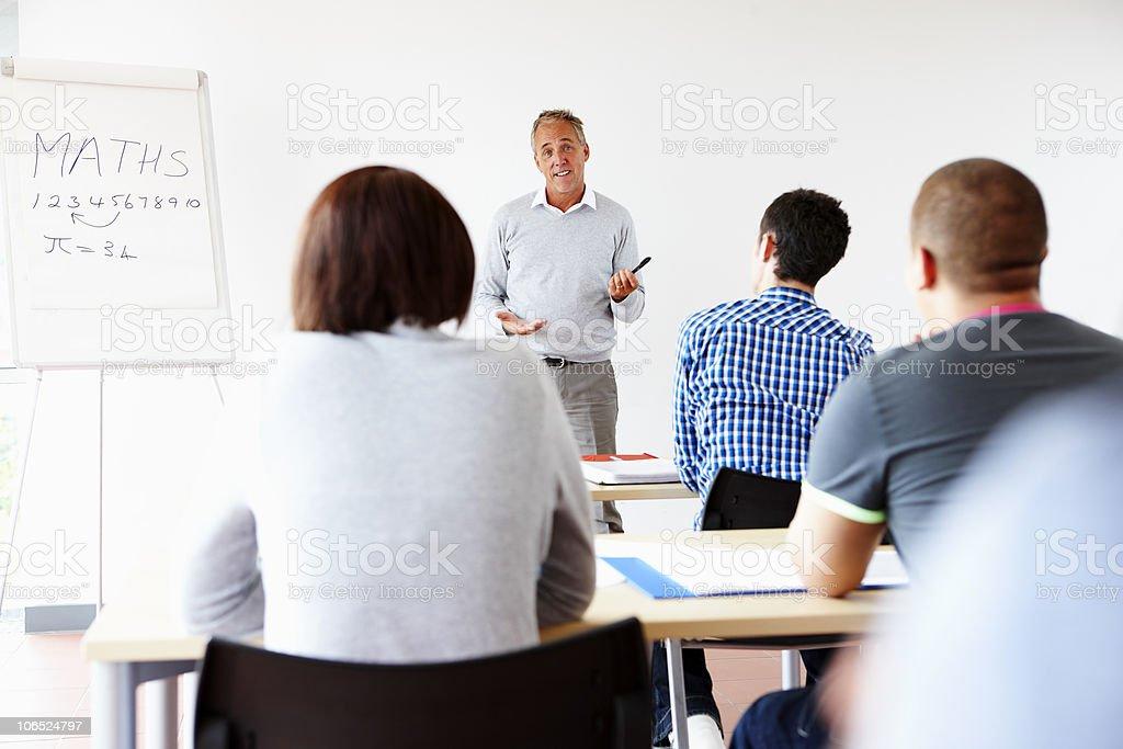 confident mature teacher giving presentation to students stock photo