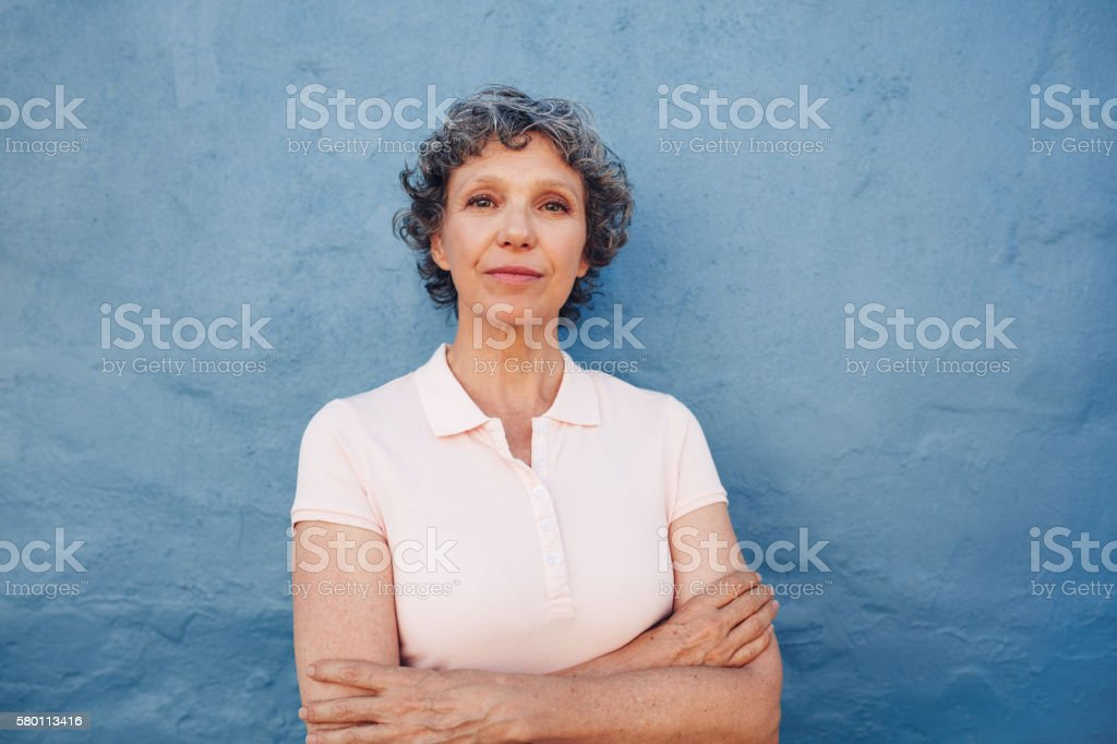 Confident mature woman standing with her arms crossed stock photo