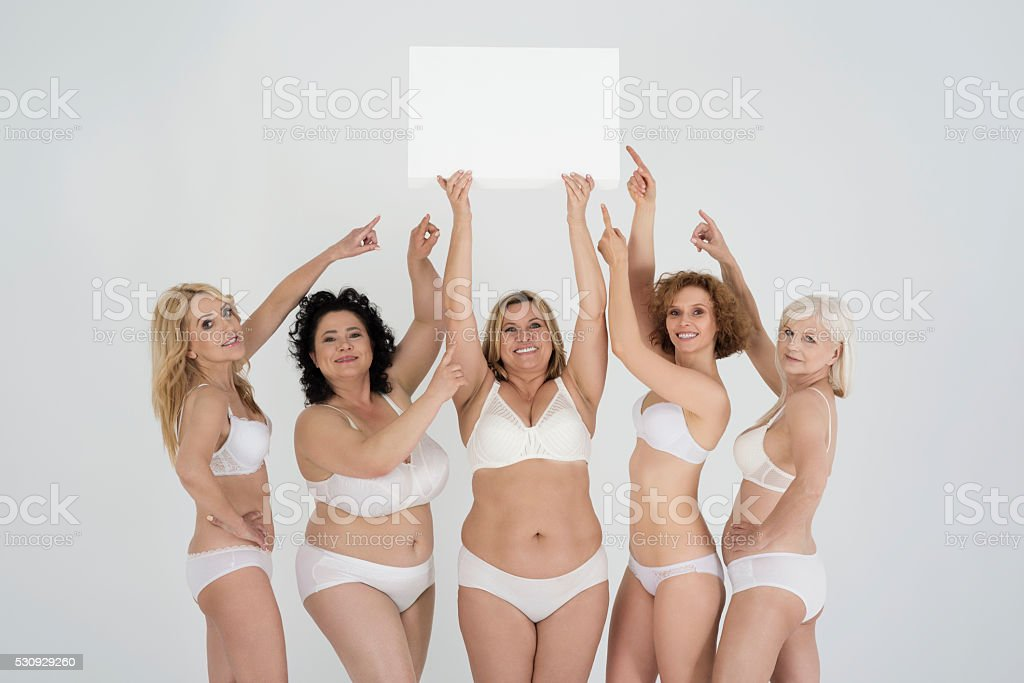 Confident mature women showing on empty white board stock photo