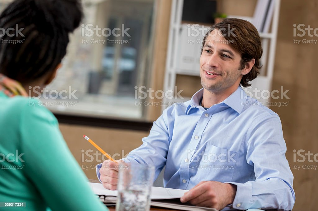 Confident mid adult Caucasian businessman meets with female client stock photo