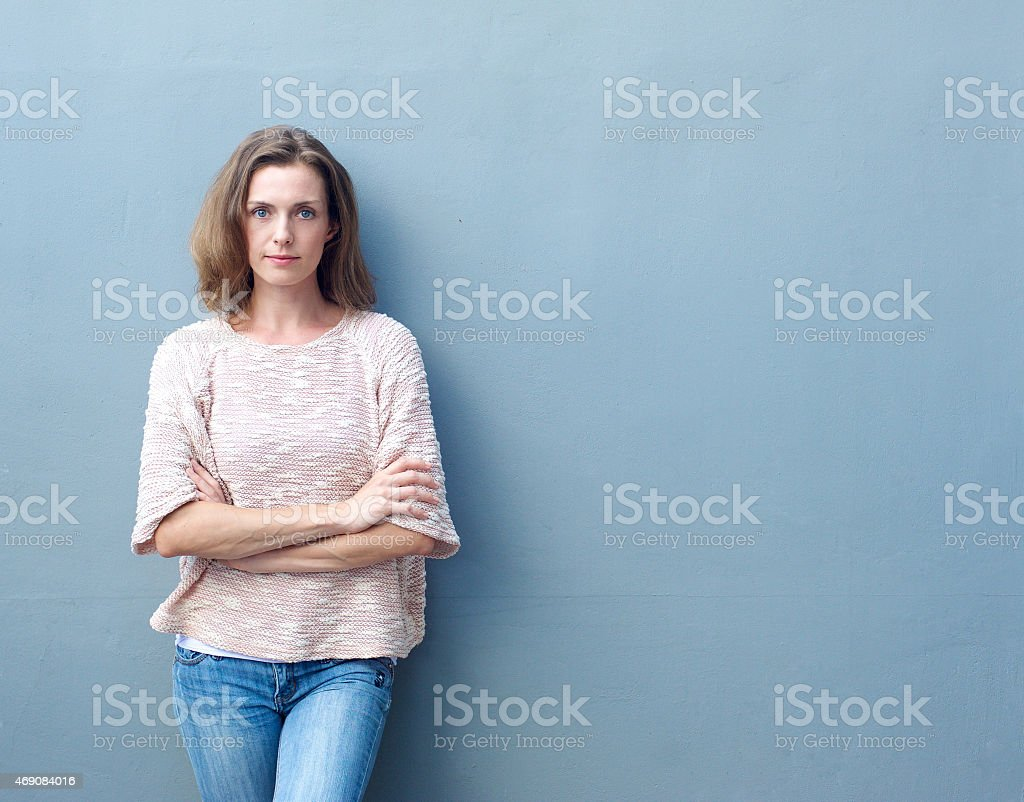 Confident mid adult woman posing with arms crossed stock photo