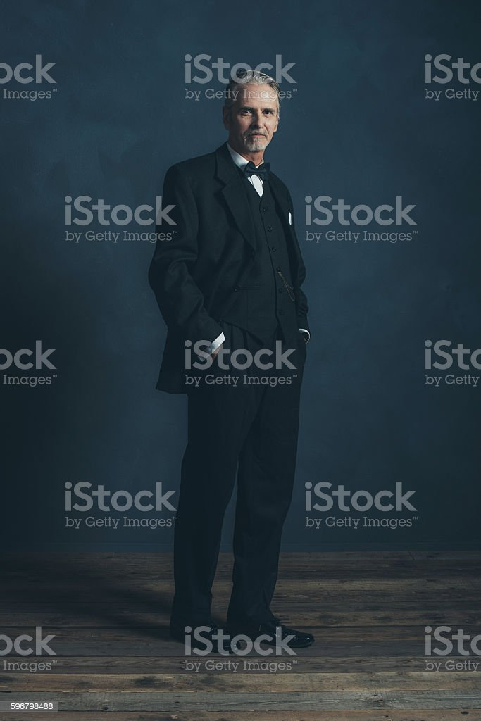 Confident middle aged retro 1920s businessman in black suit. stock photo