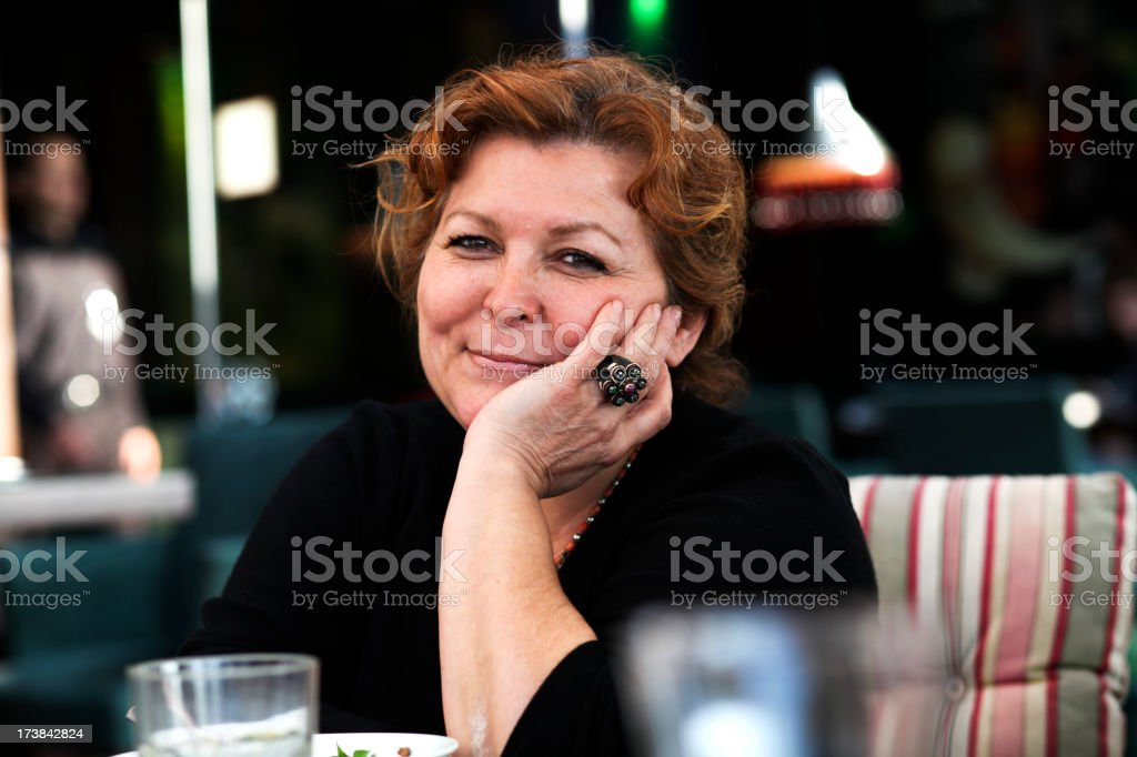confident middle aged woman is dining out royalty-free stock photo