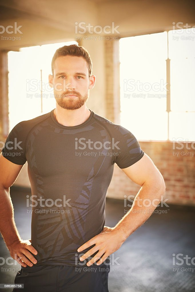 Confident muscular man standing with hands on waist in gym stock photo