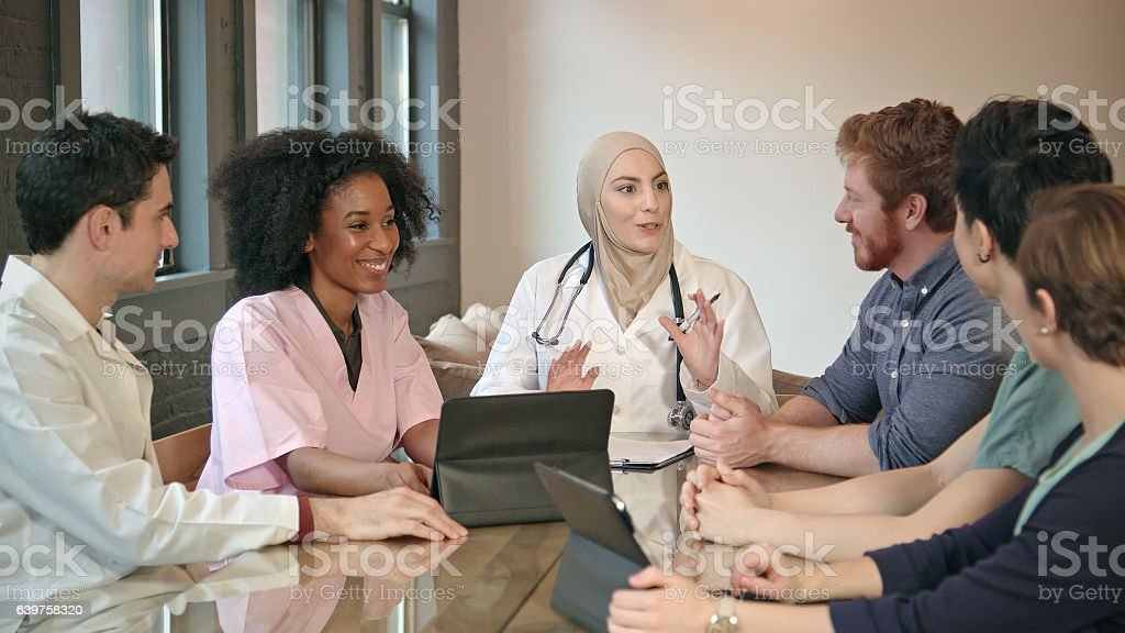 Confident Muslim Doctor Meets with Healthcare Professionals stock photo