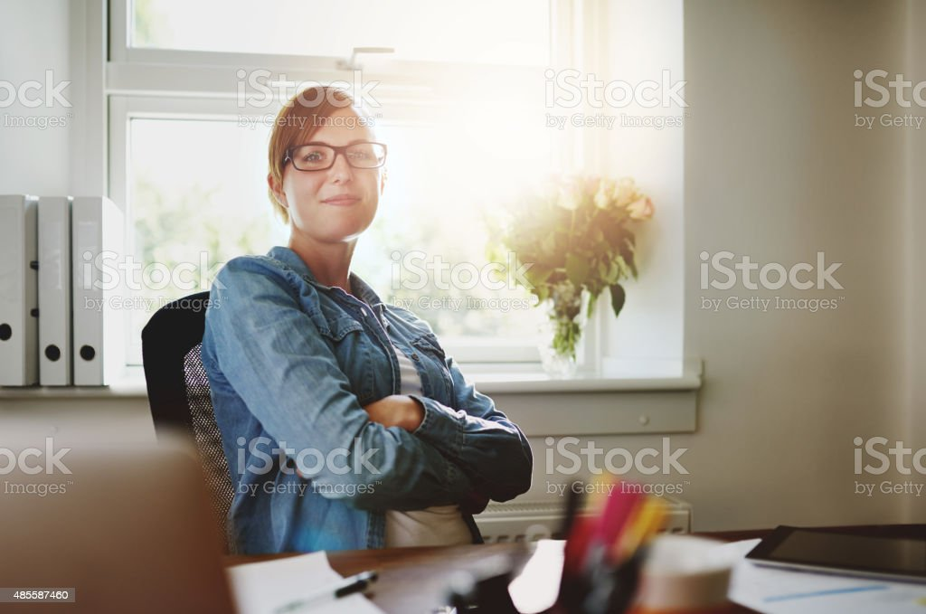 Confident Office Woman Sitting at her Desk stock photo