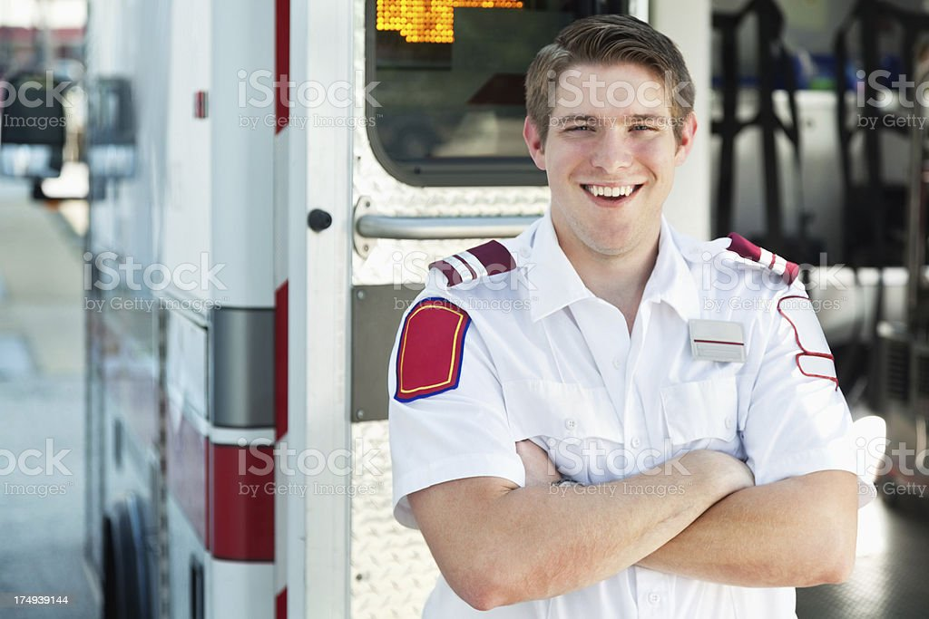 Confident Paramedic smiling in front of ambulance bus royalty-free stock photo