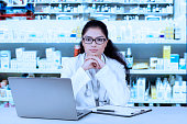 Confident pharmacist sitting in the drugstore
