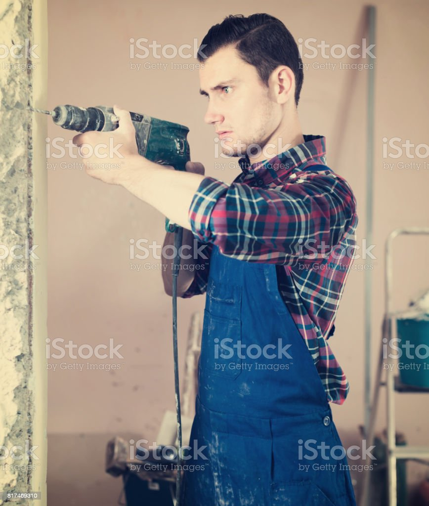 confident professional builder drilling hole in wall with perforator stock photo