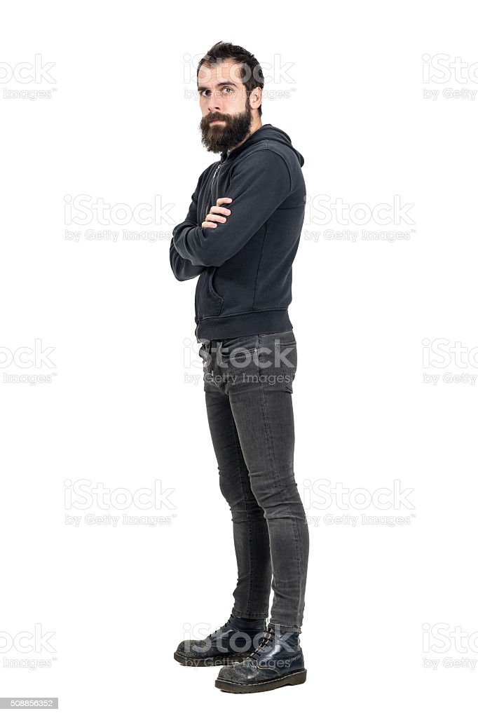 Confident punker wearing old worn boots and black hooded sweatshirt stock photo