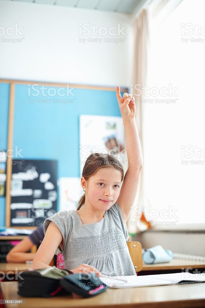 Confident school girl raising hand to answer a question royalty-free stock photo