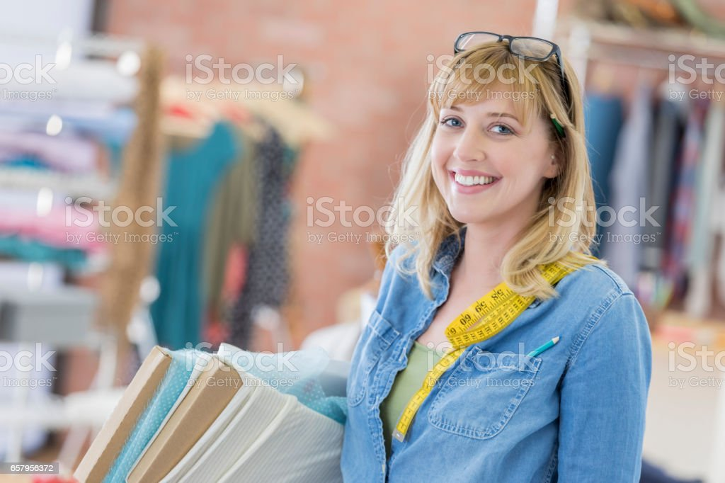 Confident seamstress with fabric stock photo