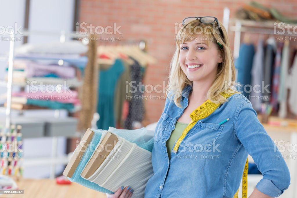 Confident seamstress with skeins of fabric stock photo