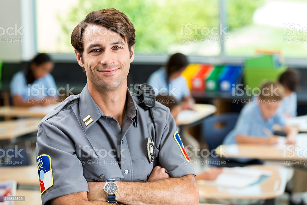 Confident security officer in front of class of children stock photo