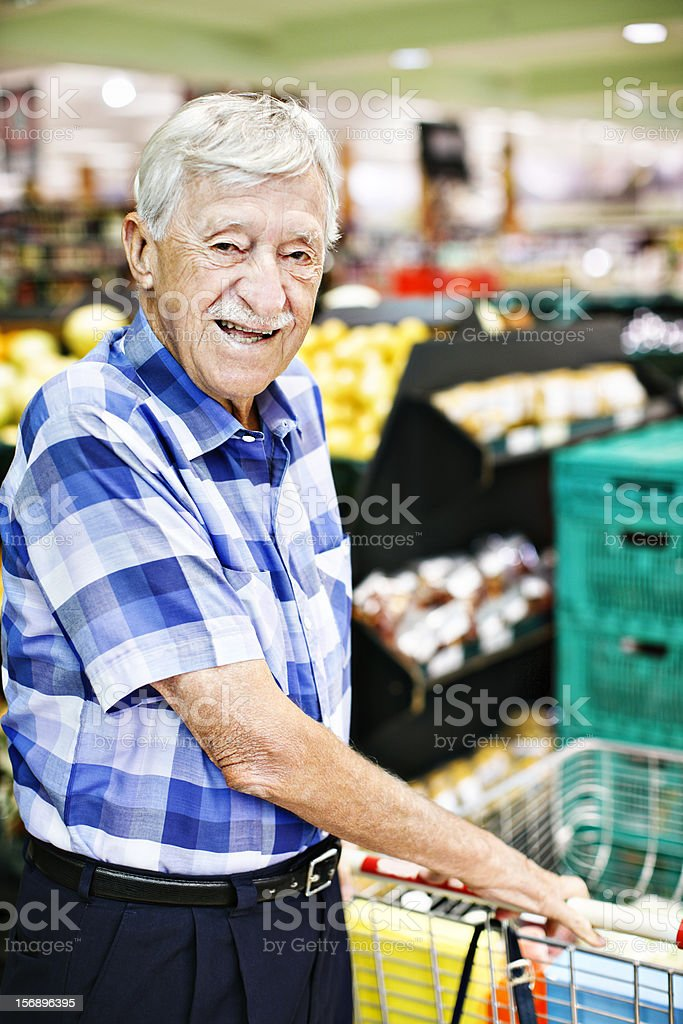 Confident senior man happily shopping in supermarket stock photo