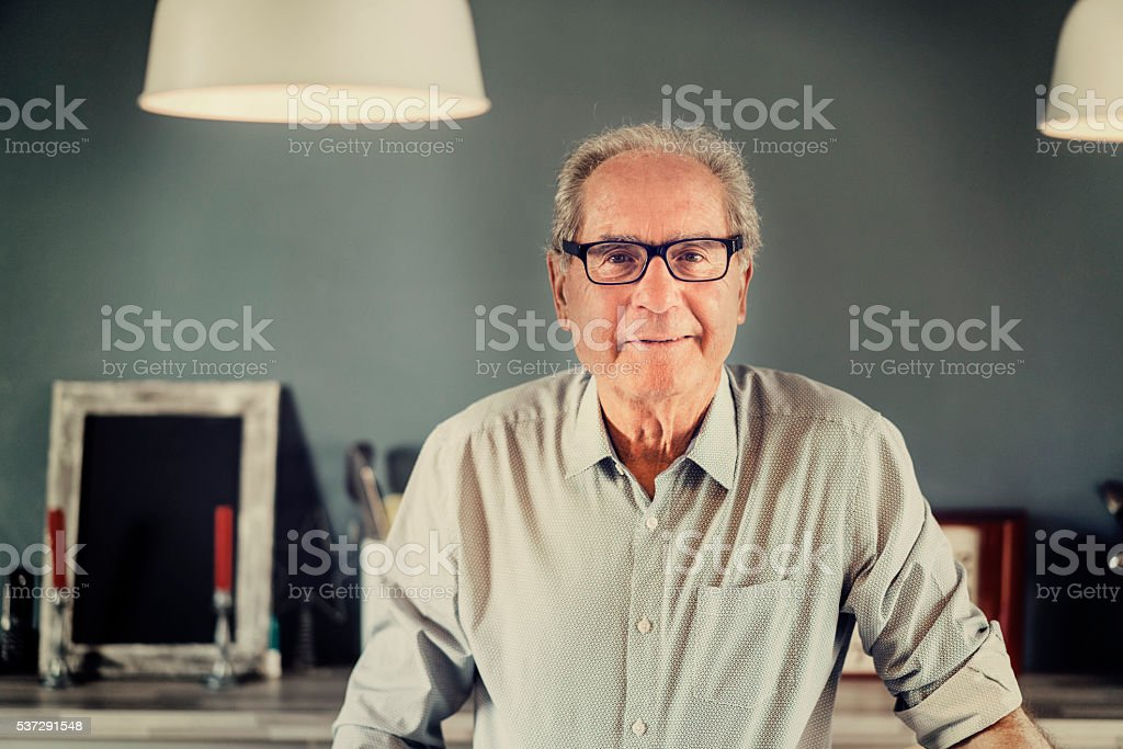 Confident senior man smiling at home stock photo