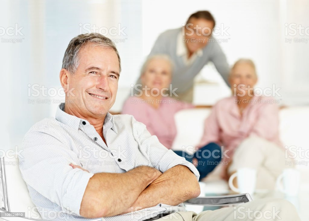 Confident senior man smiling with friends in the background royalty-free stock photo