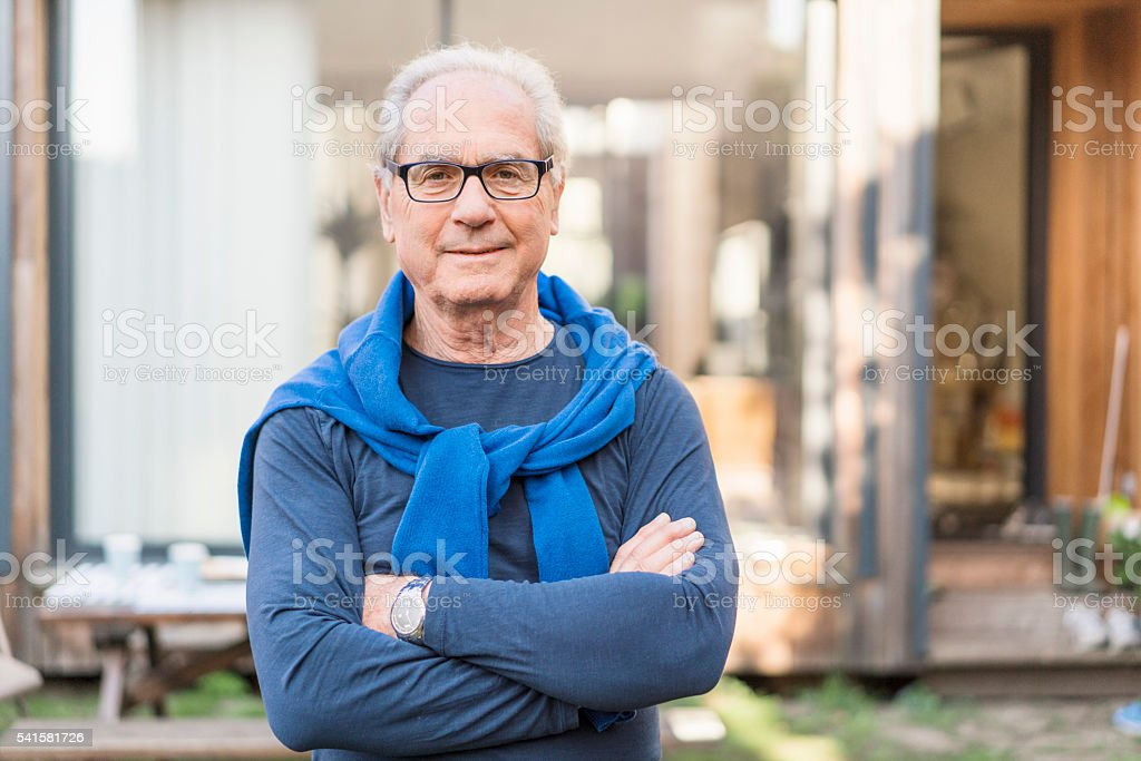 Confident senior man with arms crossed in backyard stock photo