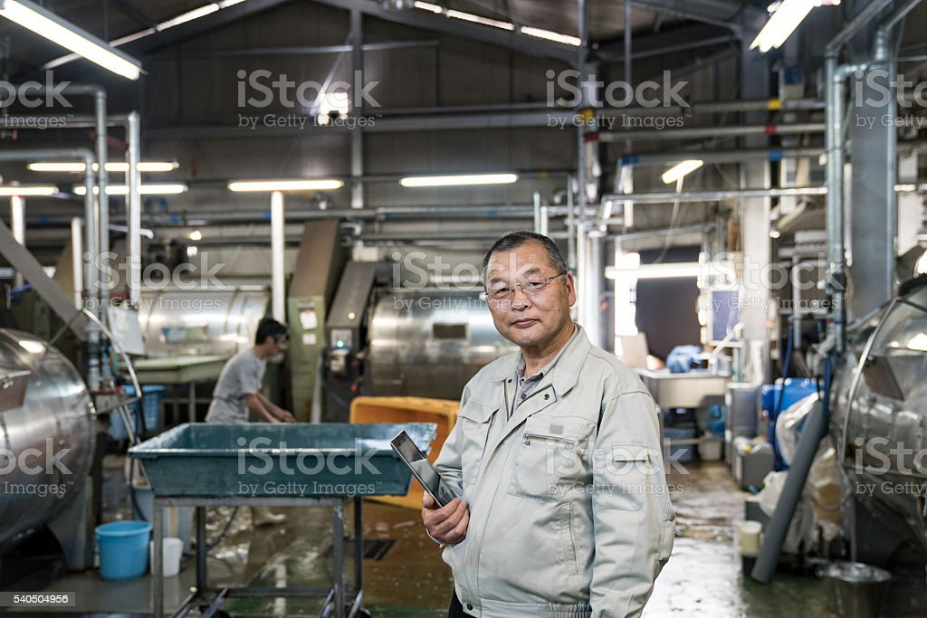 Confident senior textile industry manager holding a digital tablet stock photo