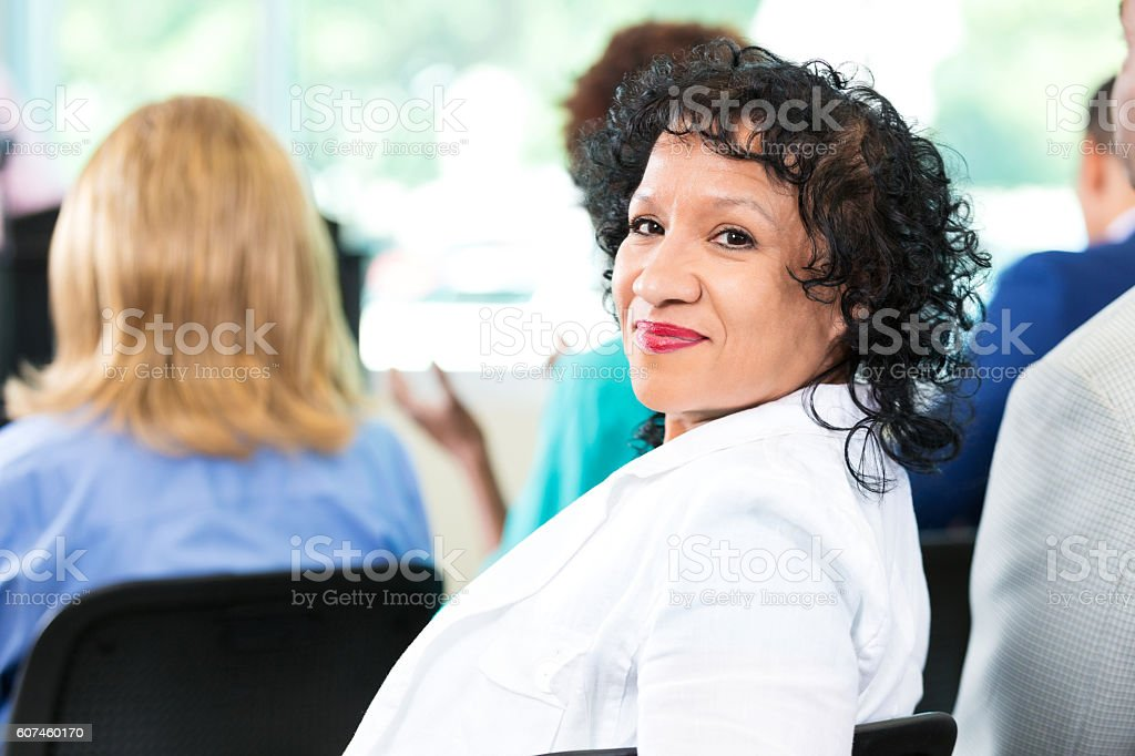 Confident senior woman participates in town hall meeting stock photo