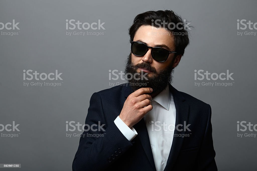 Confident serious business man fixing hair and smoking stock photo