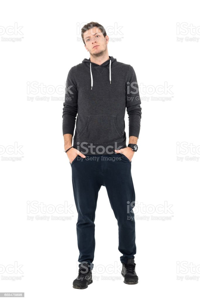 Confident serious man wearing comfortable sportswear looking at camera with hands in pockets stock photo