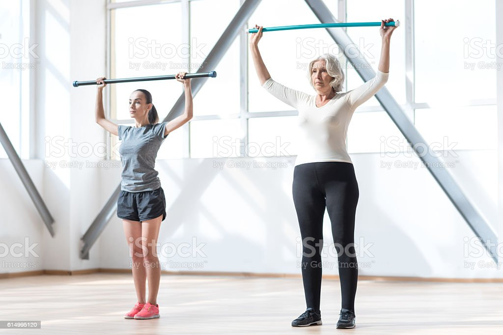 Confident serious women working out with a gymnastic stick stock photo