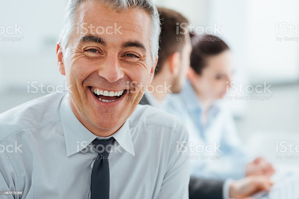 Confident smiling businessman posing stock photo