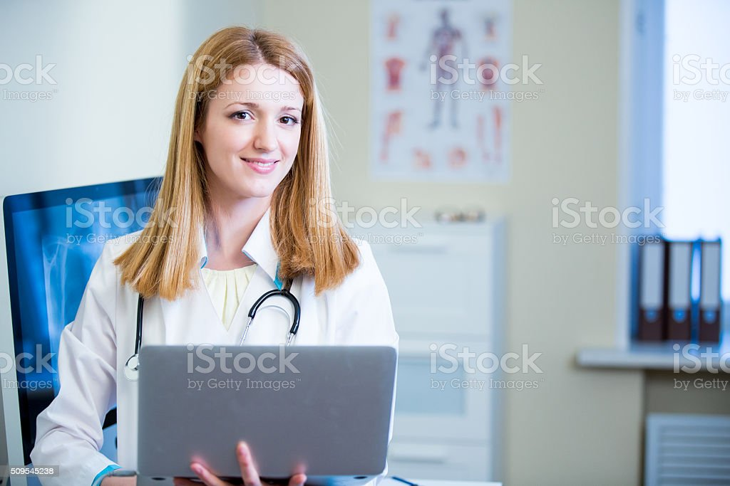 Confident smiling doctor with laptop stock photo