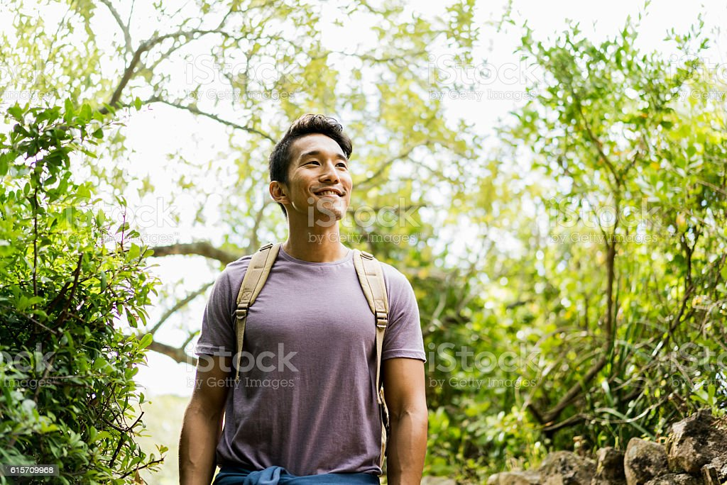 Confident smiling hiker standing against trees stock photo