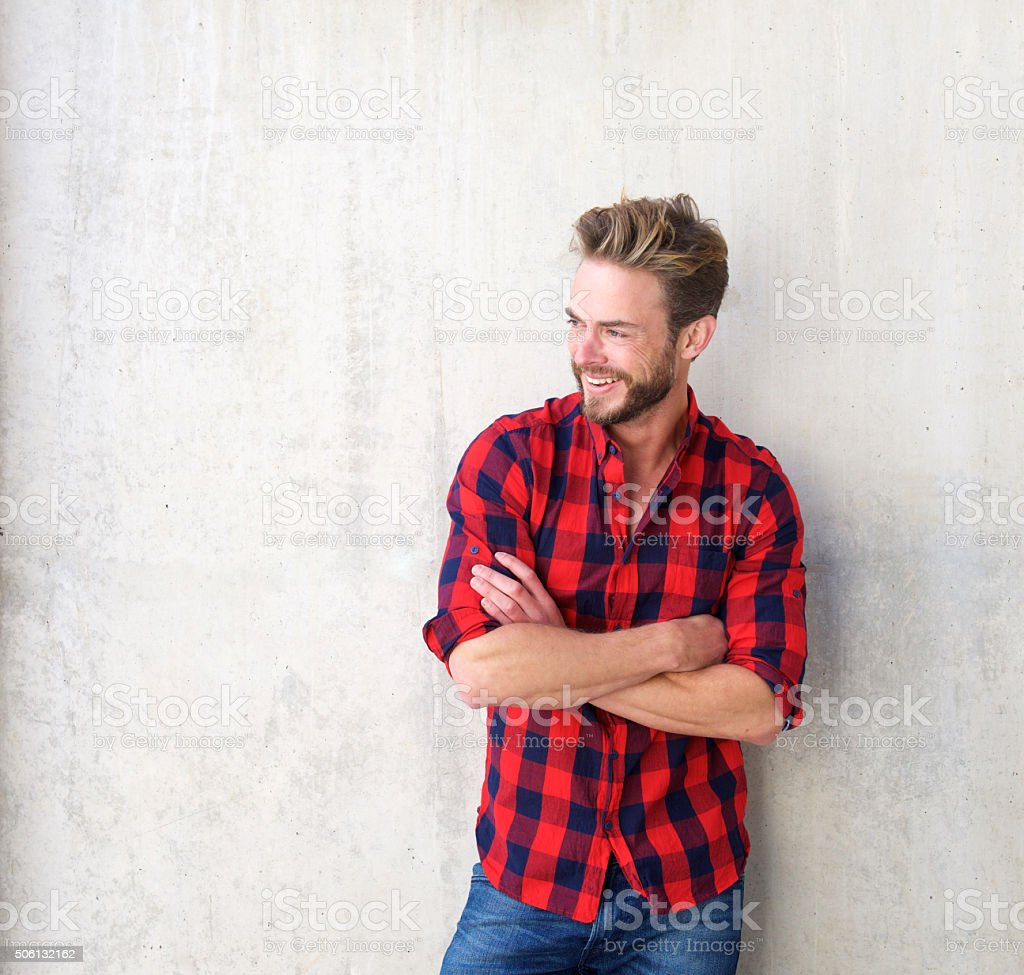 Confident smiling man posing with arms crossed stock photo