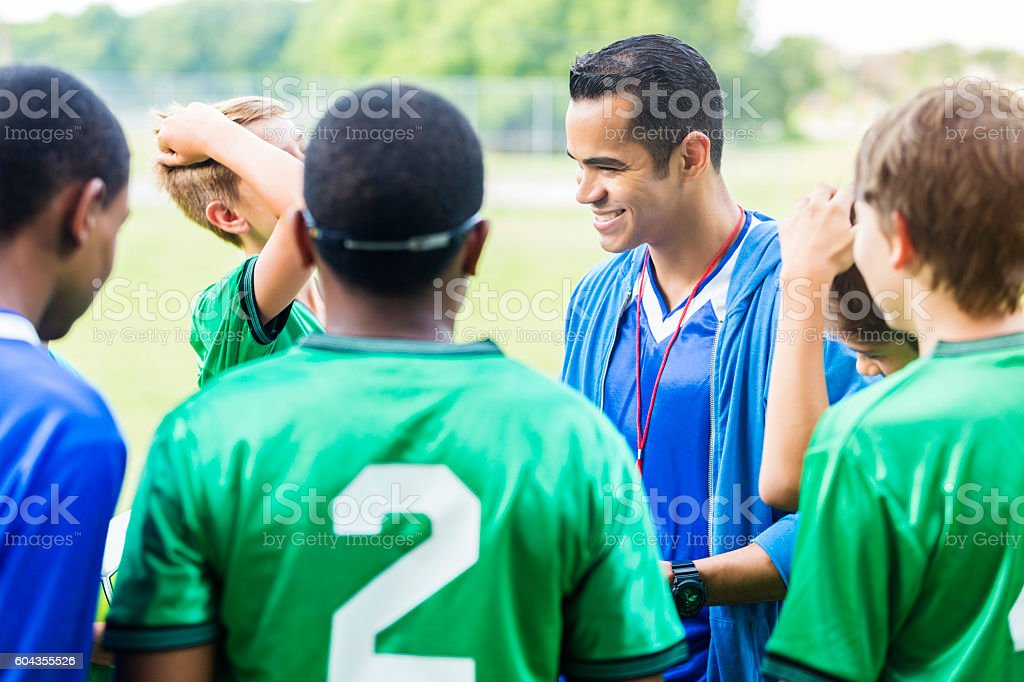 Confident soccer coach huddles with players stock photo