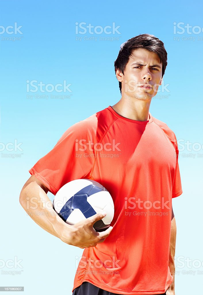 Confident soccer player with a football against sky royalty-free stock photo