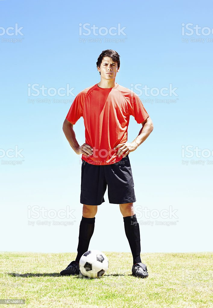Confident soccer player with a football on the field royalty-free stock photo