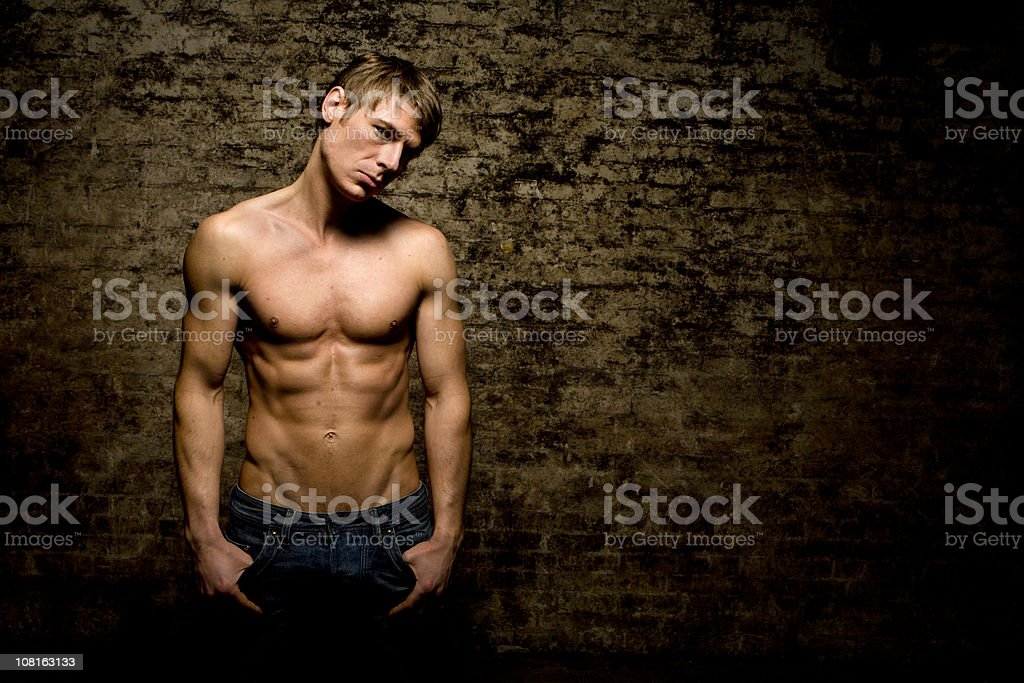 Confident stance from a muscular topless male model royalty-free stock photo