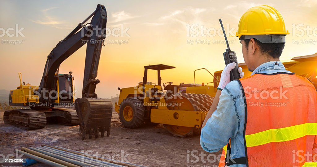 Confident supervisor using walkie-talkie at construction site stock photo