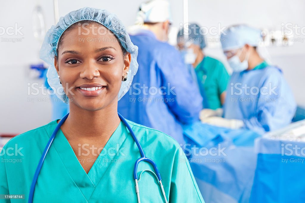 Confident surgical nurse; surgery being performed in hospital royalty-free stock photo