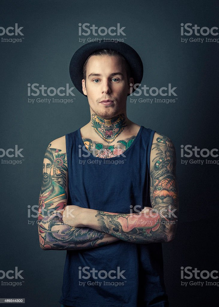 Confident tattooed man with arms crossed stock photo