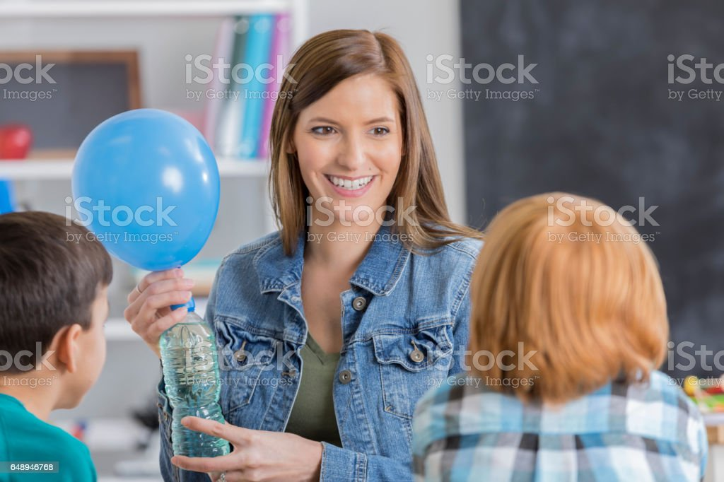 Confident teacher conducts science experiment stock photo